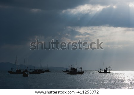 Sunlight through the clouds, a fishing boat,