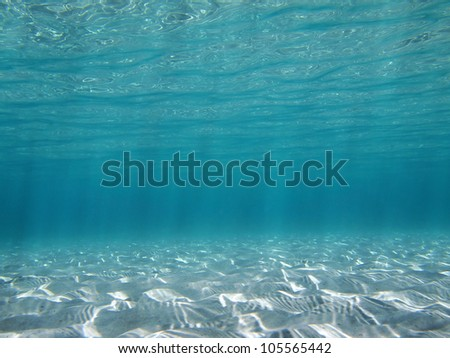 Sunlight underwater reflecting on a shallow sandy seabed in the Caribbean sea - stock photo