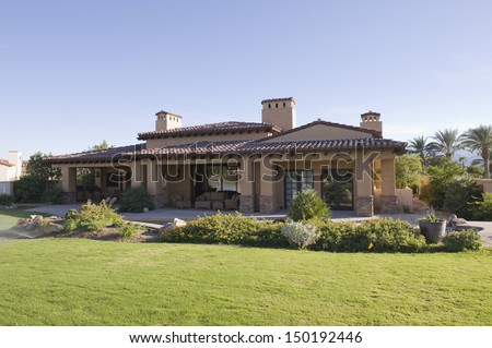 Sunlit garden exterior of home against clear sky - stock photo
