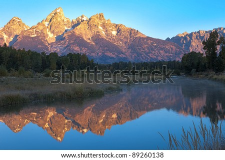 Sunlit Grand Teton reflection in Snake River. HDR composition.