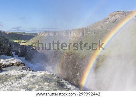 Sunlit Gullfoss waterfall in Iceland with a beautiful double rainbow forming in the sunlight through the spray - stock photo