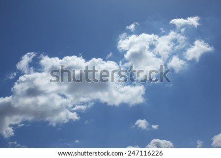 Sunlit light white clouds in blue sky - stock photo