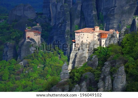 Sunlit monastery of Roussanou surrounded by dark mountains, Meteora, Greece - stock photo