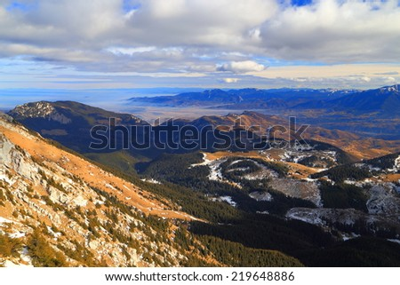 Sunlit mountain slope and distant valley at sunrise - stock photo