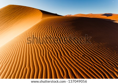 Sunlit Namibian desert dunes sand ripple pattern rises to top ridge. This desert is the oldest in the world completely devoid of surface water. - stock photo