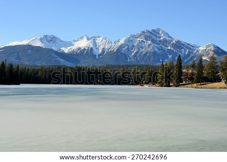 Sunlit Peaks of the Rocky Mountains Behind Beautiful Frozen Lake - stock photo