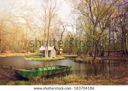 Sunlit pond with fishing boat - stock photo