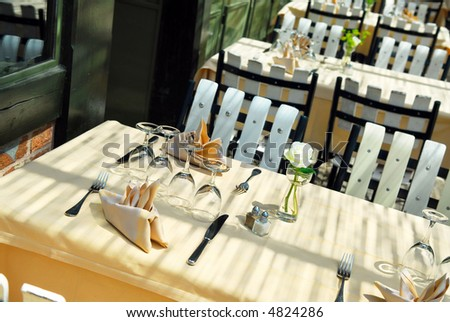 Sunlit restaurant patio with several set tables - stock photo