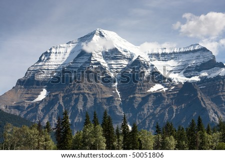 Sunlit trees in front of snow covered Mount Robson near Jasper, Canada - stock photo