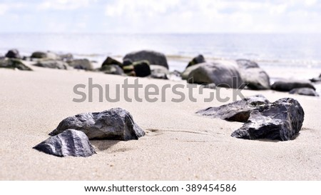 Sunny beach scene with selective focus of a rock n the sand. Horizon over water, sea scene. Close-up and selective focus of pebbles or stones at the beach. tranquil scene. - stock photo