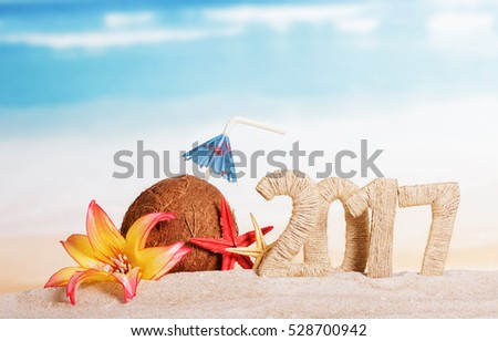 Sunny beach with an inscription 2017 Christmas coconut and starfish on sea background