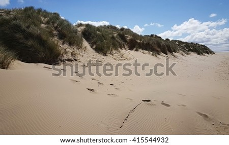 sunny beach with sand dunes and blue sky - stock photo