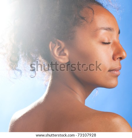 sunny beautiful mulatto woman with closed eyes on sky background