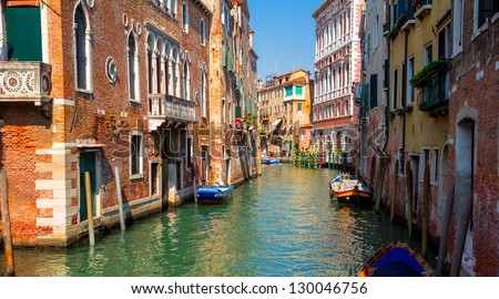 Sunny channel in Venice with boats parked around. - stock photo