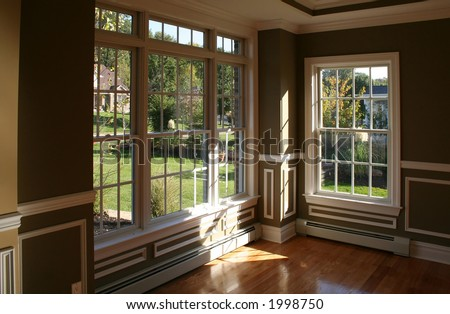 Sunny corner in living room with garden view through beautiful windows