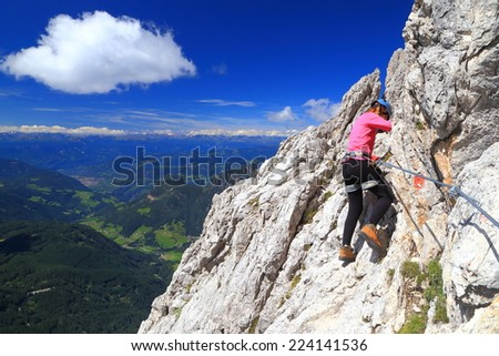 "Sunny day and woman climbing on via ferrata ""Passo Santner"", Catinaccio massif, Dolomite Alps, Italy"