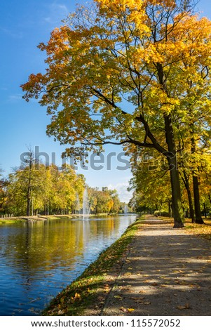 Sunny day in autumn near park and river - stock photo