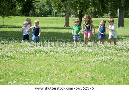 sunny day in the park with children playing - stock photo