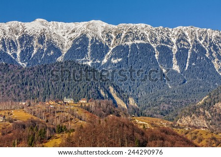 Sunny day in the valley of snowy Piatra Craiului mountains range, Brasov county, Romania. - stock photo