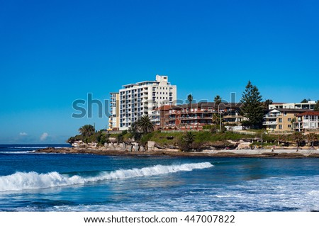 Sunny day on Cronulla beach, Australia. Urban beach with sand and rock shore with water view property on the background. Cronulla, NSW, Australia