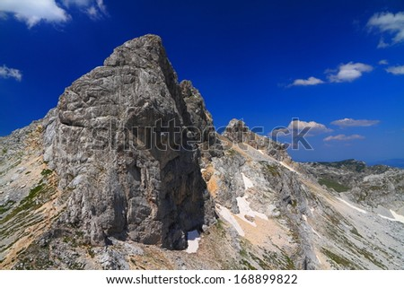 Sunny day on limestone mountain summit and nearby valley - stock photo