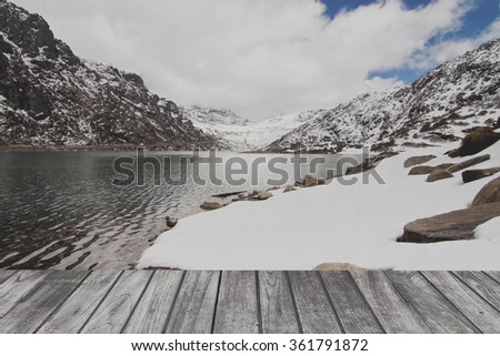 Sunny day with landscape of lake and snow mountain on wood terrace. Ready for product display montage. - stock photo