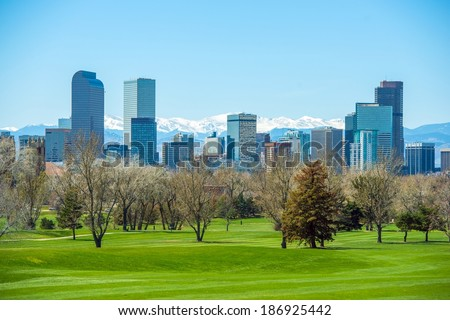 Sunny Denver Skyline. Spring in Colorado. Denver Skyline and Snowy Rocky Mountains.  - stock photo
