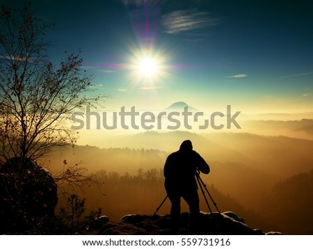 Sunny early winter  morning. Photographer preparing camera on tripod. Snowy rocks, in valley bellow colorful leaves forest. View over misty and foggy valley to Sun.