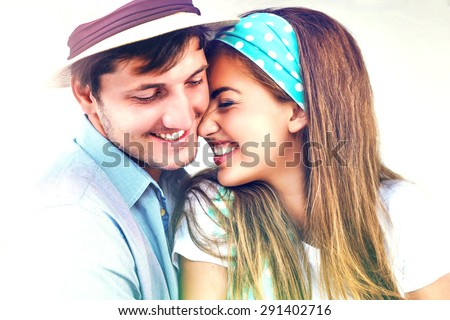 Sunny fashion lifestyle portrait of young hipster couple in love, hugs, smiling, laughing, having fun together, vintage colors, lights effect. - stock photo
