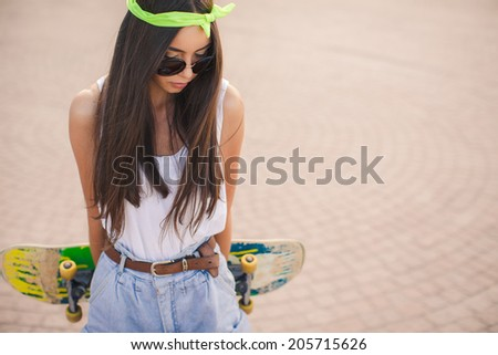 Sunny fashion outdoor urban portrait of pretty brunette fashion woman in city. Beautiful hipster girl with skate board wearing sunglasses. Beautiful and fashion young woman posing with a skateboard - stock photo