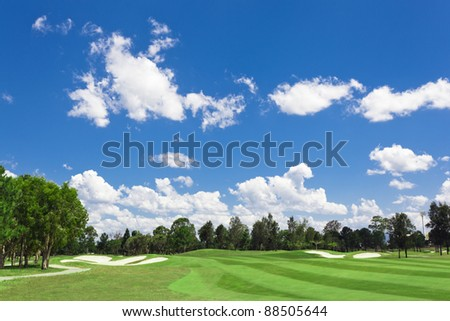 Sunny golf green with scattered clouds on a blue sky and forest - stock photo
