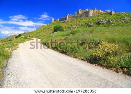 Sunny Greek road and Venetian fortress built on top of hill, Argos, Greece - stock photo