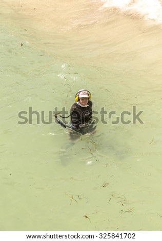 SUNNY ISLES BEACH, USA - AUG 17, 2014: man searches with metal detector  for treasures at the beach in Sunny Isles. Water metal detecting became a famous sport in the us due to cheap detectors. - stock photo