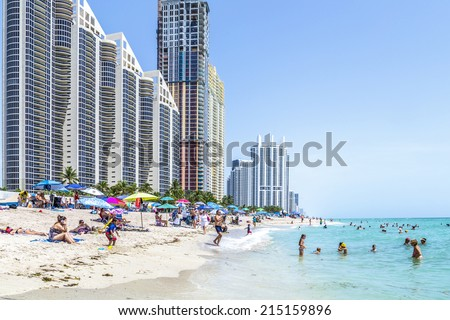 SUNNY ISLES BEACH, USA - AUG 17, 2014: people at Jade beach. Jade Beach and Ocean were completed in 2009 with a elevation of 549 feet located at 170th Street in Sunny Isles Beach. USA. - stock photo