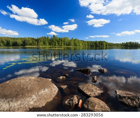 Sunny lake landscape from finland - stock photo