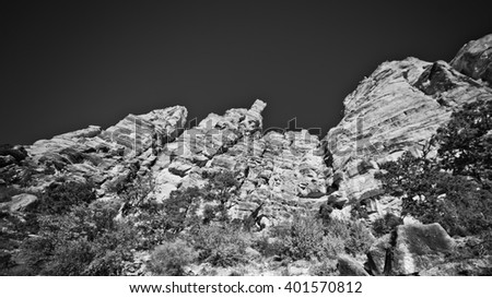 Sunny landscape of rocky mountainside at the famous hiker destination place the Ooh Aah point with clear dark sky in the Grand Canyon, USA, black and white image
