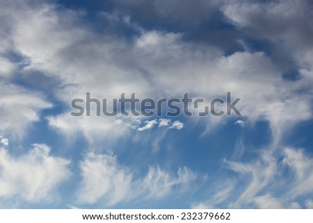 Sunny late day with white clouds of differing shapes and textures in blue sky/Sunny Afternoon Skyscape with White Clouds of Various Formations in Azure Sky/White cloud shapes and sizes in blue sky - stock photo