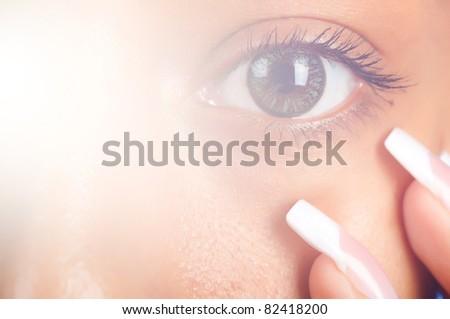 sunny macro photo of a female eye and fingers - stock photo