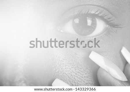 sunny macro photo of a mulatto female eye and finger nails - stock photo