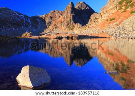 Sunny morning with mountains reflected by blue lake