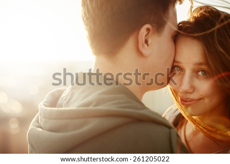 Sunny outdoor close up portrait of young happy stylish couple hugging on the roof at sunset. Selective focus. Shallow DOF.  - stock photo
