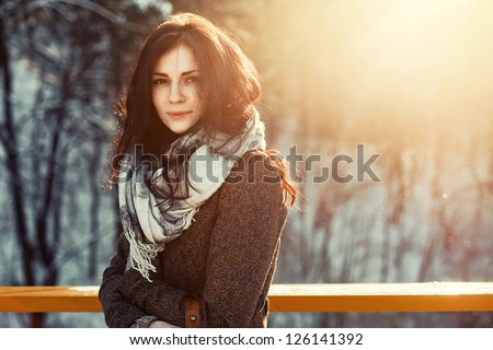 Sunny outdoor winter portrait of young attractive woman. Pretty girl smiling in winter on the street. - stock photo