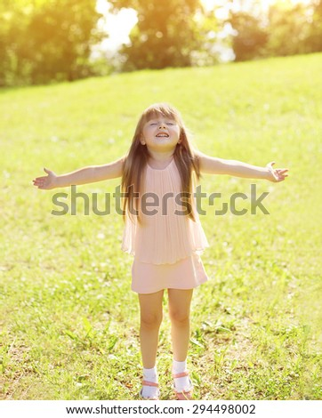 Sunny photo happy little girl child enjoying summer day and having fun outdoors - stock photo