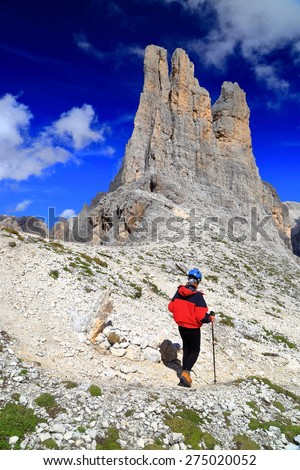 Sunny pillars of Vajolet towers above rocky trail and isolated mountaineer, Catinaccio massif, Dolomite Alps, Italy - stock photo