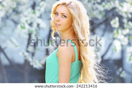 Sunny portrait lovely blonde girl in spring garden, blooming tree, clear warm day - stock photo