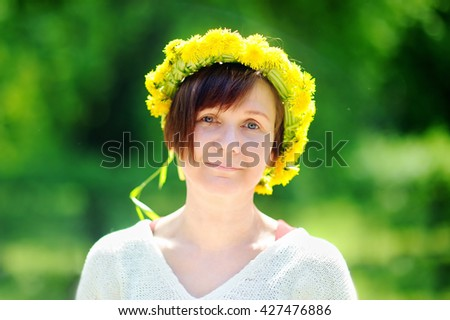 Sunny portrait of beautiful middle age woman with dandelion wreath