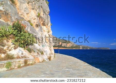 Sunny promenade along limestone mountain side on the sea shore in Nafplio, Greece - stock photo