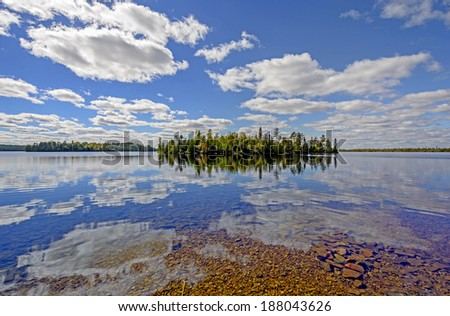 Sunny Reflections on Kekekabic Lake in the Boundary Waters - stock photo