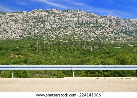 Sunny roadside with limestone mountains spotted with green bushes on the Dalmatian coast, Croatia - stock photo