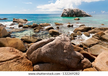 Sunny rocky ocean shore and and uninhabited little rock island in the beach of Seychelles Islands - stock photo